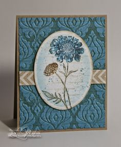 """By Lynn Weiss. Background: Ink """"Beautifully Baroque"""" embossing folder with Crumb Cake. Insert Marina Mist cardstock and emboss. Add ribbon. Image panel: Stamp flower in Marina Mist and Crumb Cake (from """"Field Flowers""""). Die cut oval from white cardstock. With die in place, sponge with Marina Mist. Remove die. Stamp with """"En Francais"""" inked in Crumb Cake. Add splatters from """"Gorgeous Grunge."""" Sponge edge with Crumb Cake. Assemble on card base."""