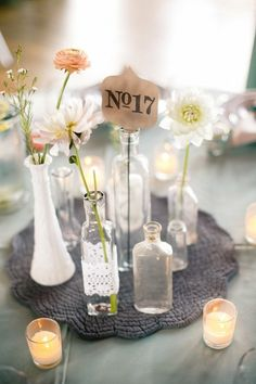 Mismatching clear bottles and jars (no coloured ones, clear only). Bottles to have long stem white/cream flowers in them (one type of flower only, different sizes is fine) and jars with candles in them. The jars may also have water with candle floating on top.