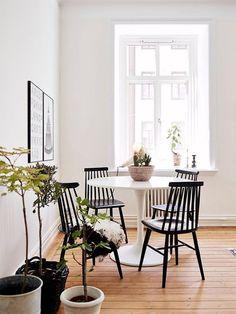 sala de jantar minimalista com vasos de plantas e mesa tulipa