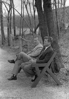 President John F. Kennedy (right, holding pipe) sits on a bench with Under Secretary of the Navy Paul 'Red' Fay at Camp David - 1963