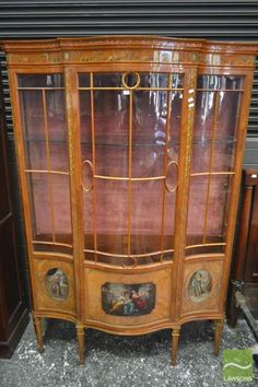 Good Late Victorian Satinwood Bow Front Display Cabinet, painted with festoons & Kauffmann style panels, having astragal door and side panels, on tapering legs - faults with back legs (Key in Office)