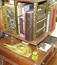 This is an English brass and wood Revolving Book Caddy for a desk. The inkwell in the picture is my smallest hinged top in vaseline glass also called uranium glass. It will glow a bright green under black light.  Judith Walker's Collection