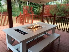 An outdoor table with a built-in cooler and a fire pit.