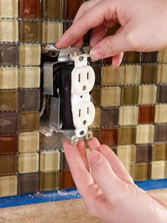 "Tip on installing kitchen backsplash tiles: ""Dealing with Switches and Receptacles    Switch off the power at the breaker panel, unfasten the two screws holding the switch or receptacle, and gently pull it away from the wall. When tiling and grouting are complete, add a box extender as shown. Because of the extra thickness of the tile, you might need longer screws."""
