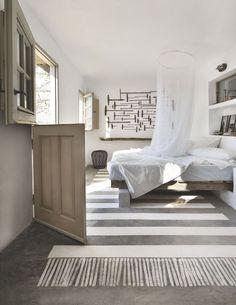 Une chambre avec un faux tapis peint sur le béton et une collection murale d'outils de charpenterie de marine.