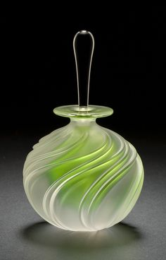 Apple Green Swirl Perfume by Mary Angus. A bright green core glows within this elegant *blown glass* perfume bottle, highlighting its carved spiral design. A clear glass stopper contrasts beautifully with the bottle's frosted surface. Signed on bottom.