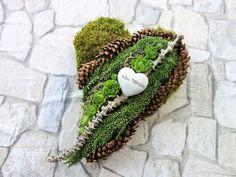 Dieses Herz ist ein besonderes Gesteck für Totensonntag oder Allerheiligen. Es wird als haltbarer Schmuck für den Winter auf dem Grab abgelegt.    Auf einem Herz aus grünem Moos sind kleine Zapfen, weißes Heidekraut, grüne Sempervivum Rosetten und etwas Graumoos dekoriert. Ein