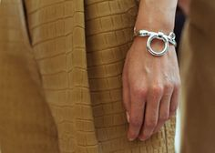 Solid bracelets at Hermès. In conclusion of work as a creative director at Hermès, Christophe Lemaire added to his ivory and sand-colored images the solid silver jewelry, designed by Pierre Hardy.
