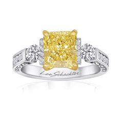 Make a truly glamorous statement with this remarkable engagement ring, featuring a cushion-cut rare, fancy yellow diamond bordered by two ro...