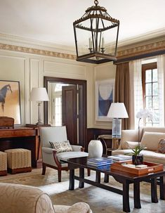 An oversized lantern hangs above this beautifully appointed living room - Traditional Home