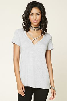 HATE these shirts:  A heathered knit tee featuring a V-neckline with strappy cutouts and short sleeves.