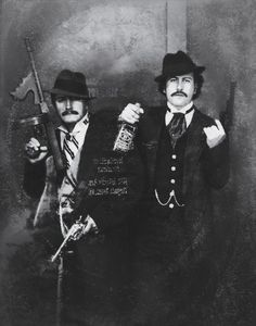 Pablo Escobar (right) 'posing' as a gangster with his cousin Gustavo in the 1980s.