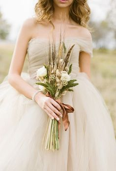 A rustic bouquet made of white roses, wheat, greenery, and feathers, tied with a silk ribbon, created by Victorian Gardens.