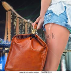 Tourist woman adventure with luggage in Singapore. Summer travel. Background of Marina Bay Sands