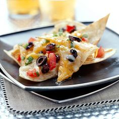 Party Nachos  Tortilla chips are piled high with two different cheeses, green onion, tomato, diced green chile peppers, olives, and black beans.