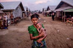 Oma Salema (12) sostiene a su hermano desnutrido Ayub Khan (1) en un campamento para rohingya en Sittwe, Myanmar. 5 de junio de 2015. El gobierno de Myanmar dice que está decidido a detener las salidas de los migrantes que huyen de la persecución religiosa en lugares como Sittwe , pero no va a ceder en su negativa a responder a las condiciones de conducción del éxodo a través del mar. Tomas Munita—The New York Times/Redux