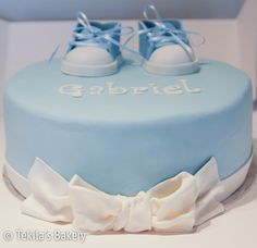 Christening cake with wite bow and blue baby shoes