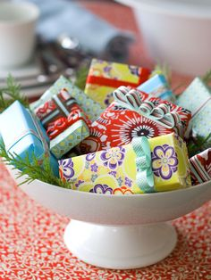 A basket of beautifully-wrapped gifts serves two purposes: It's a bright, festive table centerpiece and a source of treats for unexpected guests. {lip balm, small lotions, Legos, earrings, matchbox cars, 100 other ideas in my head.....}