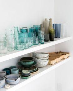 white shelves with colorful glassware and ceramic dishes inside erin scott's photography studio in Berkeley, California. #ceramics #glassware #glasses #storage #openshelves #shelving #wallstorage #studio #whiteshelves