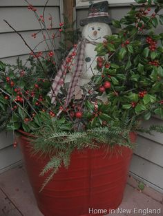 Old Red Bucket...stuffed with Christmas greenery & a...snowman.