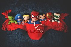 Spiderman's a popular choice! Another baby is pictured alongside toy replicas of his super...