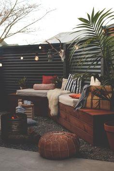 焚き火台とベンチのあるシンプルな庭の屋外リビング
