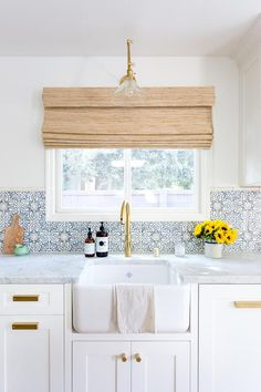 White shaker kitchen cabinets are beautifully complemented with brass hardware and a white marble countertop fixed on either side of a farmhouse sink fitted with a Newport brass faucet.