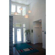 Petros Homes. Modern Contemporary Home. Vaulted ceiling entry, glass bead pendant chandelier, colorful carpet square design, gray wood floor, stone column.