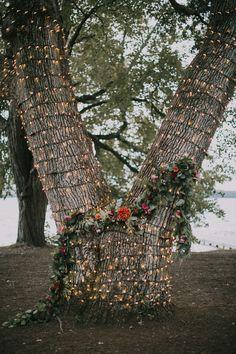 lit tree ceremony backdrop - photo by Jamie Mercurio http://ruffledblog.com/maine-summer-camp-wedding