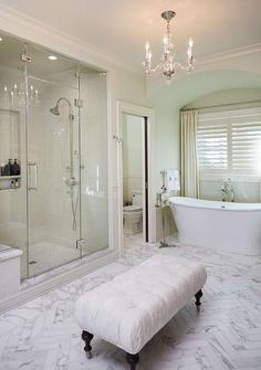 Stunning traditional master bathroom boasts a freestanding tub paced on marble floor tiles in a front of a window covered in plantation shutters and ivory curtains fixed beneath a barrel ceiling in a tub nook fitted with walls half tiled with light gray backsplash tiles.