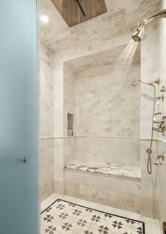 A frosted glass door opens to a walk in shower filled with cream marble tiles fitted with a ceiling mount rain shower head as well as two wall mounted shower heads over a cream and black mosaic shower floor. Cream Marble Tiles, Shower Tile, Frosted Glass Door, Shower Bench, Walk In Shower, Bathroom Design Small, Shower Floor, Walk In Shower Enclosures, Shower Heads
