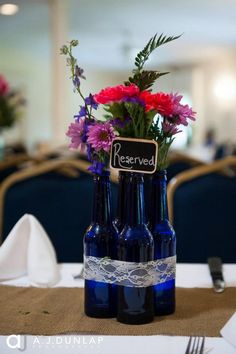 I handmade my reception centerpieces and table runners. The center pieces were made of four Bud Light Platinum bottles hot glued together and accented with lace ribbon. The fresh flowers were ordered through Costco and my husband's great aunt arranged each centerpiece. I measured and cut each burlap table runner by hand. I also accented the center pieces with plain glass votive candles holders hand wrapped in the same lace pictured above.