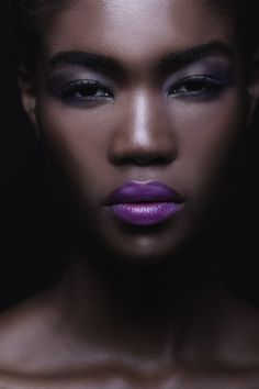 beauty and makeup image of black model with purple lipstick