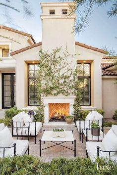 One of the home's many outdoor seating areas is arranged to take full advantage of the limestone fireplace from Casa de Cantera. The pillows on the homeowners' iron-frame chairs were refreshed with Perennials fabric from John Brooks Incorporated.