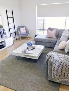 Contemporary and stylish living room with grey and white furniture and pops of colour in cushions and decor