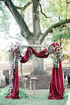 The end of the aisle is where the most important moment in your wedding takes place. Make sure it fits your style as a couple. This red velvet drape makes for a memorable ceremony backdrop. | Luxurious Velvet Details for Wedding Inspiration