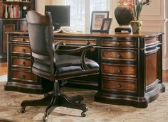 Two-toned wood office desk with leather office chair on wheels