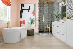 HGTV features a pink master bathroom with a light hardwood floor, soaking tub, custom artwork and black-and-white-tiled walk-in shower.