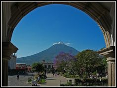 """Antigua, Guatemala. Agua Volcano is seen here through one of the countless arches in the city. The volcano was sending """"smoke signals"""" during the time visiting the area. Local architecture has a strong Spanish influence so arches are everywhere."""