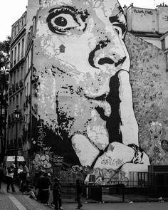 Façade d'un grand immeuble illustrée d'un visage avec l'index posé sur sa bouche, en face de la fontaine Stravinsky, à coté du centre George Pompidou, Paris.