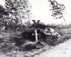 Operation Market Garden, 1944: Disabled British Sherman of the 44th Royal Division and grave of a British casualty. The helmet suggests the deceased was a paratrooper.