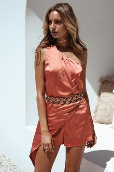 The super sexy Silky Lava Playsuit is made from a silky fabric in a burnt orange hue. It is a one shoulder style and has an asymmetric overlay feature draping over one hip and a side zip for a contoured fit! Complete the look with gold accessories and heels for your next night out! By Sabo Skirt.