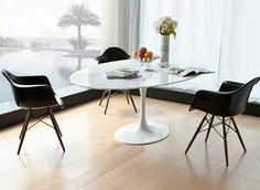 Sala de Jantar com cadeiras pretas Eames com pés de madeira e mesa branca oval