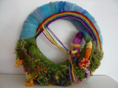Rainbow by seizoentafel Season Table needle felt creation. #Waldorf Needle felted #Rainbow Gnome swinging on rainbow with wool fleece garden. Divine