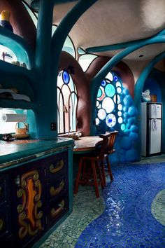 The countertops are poured concrete, and the floor is mosaic tile. At every turn: an arched ceiling and amorphous windows.