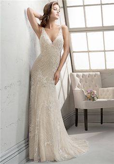 Stunning sheath dress of beaded embroidered lace appliques on tulle over Evita satin, adorned with glittering Swarovski crystals. Floral embellishments cascade the bodice and plunging illusion neckline. Finished with zipper over inner elastic closure.