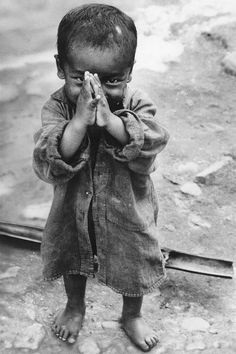 Young child hiding behind hands | Black and white street photography | travel photo