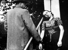 Public execution of Herta Kašparová, a brutal Gestapo agent, by short drop hanging. The doctor tests her pulse. Czechoslovakia, 13.9.1946.