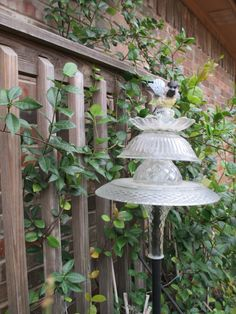 Garden totem from old plates, bowls and a vase.