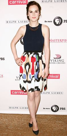 Michelle Dockery made a ladylike appearance at the Downton Abbey photocall: Victoria Beckham design a gold chain neckline, black bodice and colorful pleated skirt.